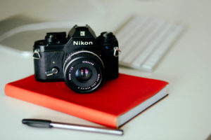 Camera on red notebook with pen and computer - picture day